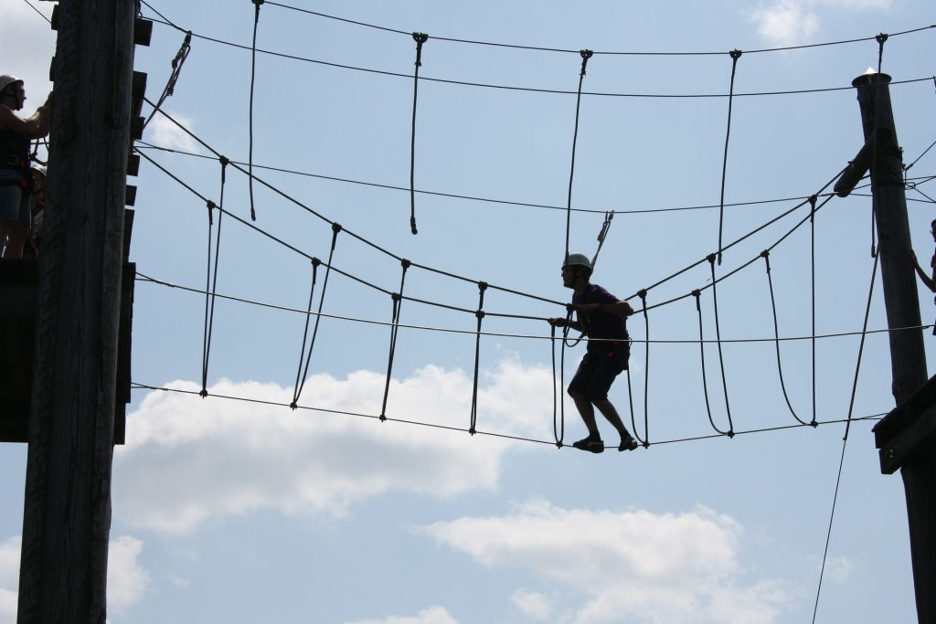ropes course in air, man with helmet doing course