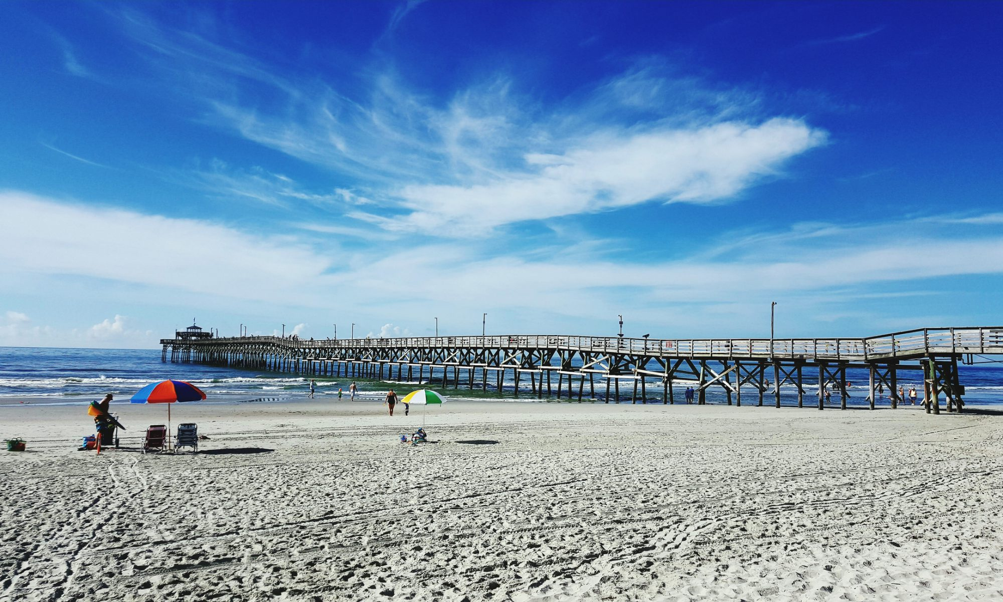 beach, pier, people on beach with umbrella