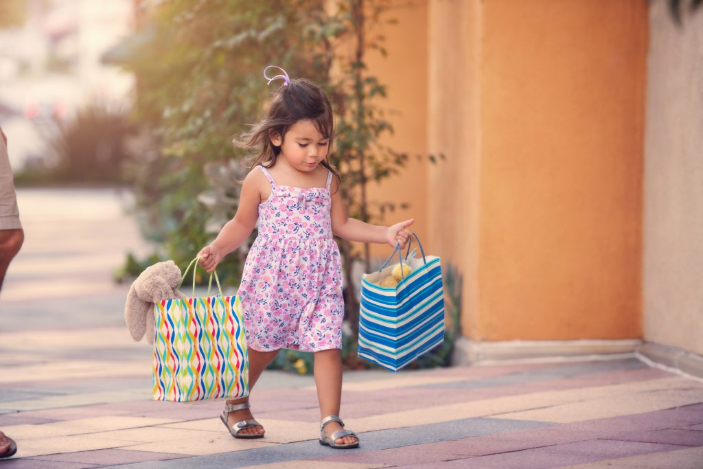 cute toddler girl, holding shopping bags with stuffed animals