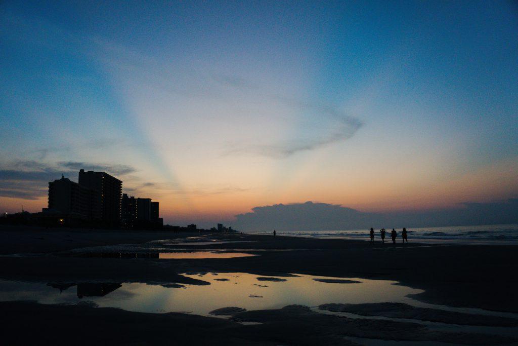 sunrise, beach, water, sand, ocean, people walking, buildings in background. clouds in sky
