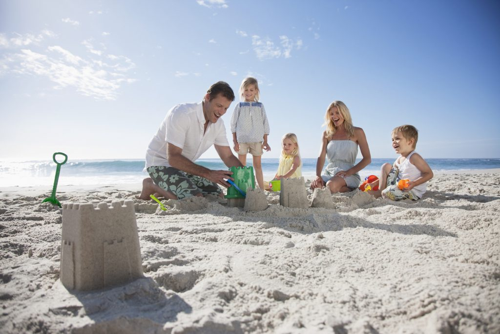 Sand, beach, family, boy, girl, man, woman, sandcastles, sand toys, water, ocean, blue sky